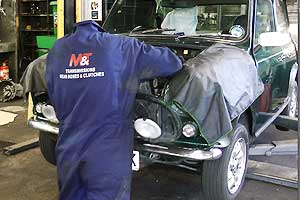 distance view of a mechanic working under the bonnet of a classic british racing green mini 1275 gt getting a service