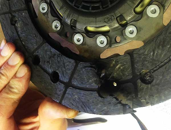 close up angled side view of a broken clutch plate that has completly split down one side highlighted by our clutch specialit pulling open the crack with his blue gloves