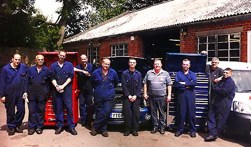 distance view of our sheffield garage and team all lined up wearing blue overalls and the company logo smiling happily outside the garage entrance