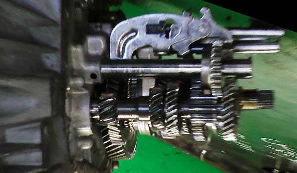 a dismantled gearbox on a metal bench showing the gearbox casing, shafts, gears and selectors all in situ for reference against our animation