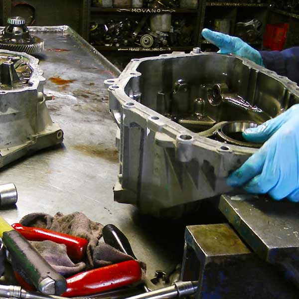 distance view of a dismantled ford gearbox showing the bell housing held and examined by an expert and various components on his bench