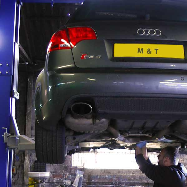 distance rear slight under and over view of a gunmetal grey coloured audi rs4 car on a ramp high in the air part way through servicing by a m and t mechanic