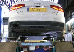 a white audi a4 high in the air on a ramp viewed from underneath receiving parts after failing its annual mot test