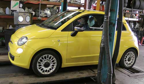front passenger side distance view of a really pretty bright yellow fiat 500 getting its annual mot test on the rolling brake test with our mot inspector at the wheel