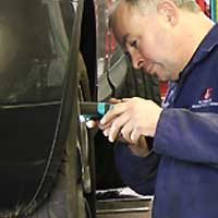 close up of an mot tester inspecting under a volkswagen rear drivers side wheel arch aided by a hand light for possible MOT failures