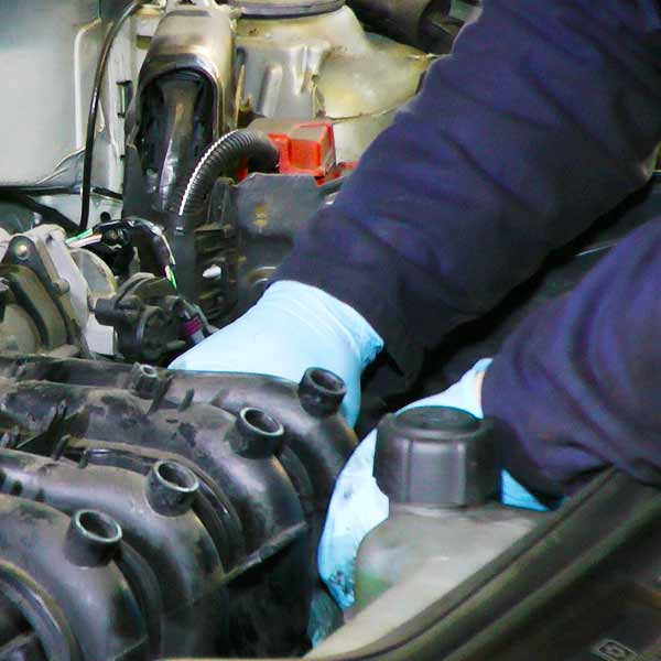 close up view from above of a mechanic servicng a volkswagen car and wearing protective blue gloves