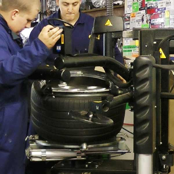 distance view of a new tyre being fitted by our tyre specialist using the lastest tyre fitting and punture repair equipment