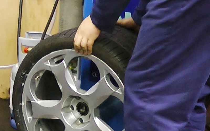 close up of a new intricately spoked alloy wheel being fitted with a new tyre